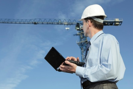 Engineer with laptop against crane